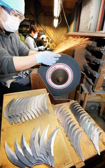 農期入りを前に職人の手で次々に研磨される鋸鎌の刃=2月19日、福井県越前市武生柳町