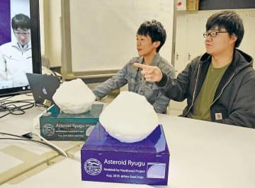 JAXAの記者会見の映像を確認する(左から)須古さん、小林さん。手前はりゅうぐうの模型=会津若松市の会津大