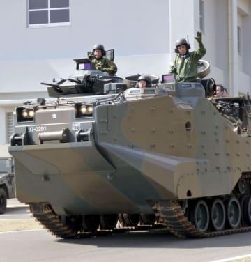 陸上自衛隊相浦駐屯地で水陸両用車「AAV7」に乗り、手を上げる岩屋防衛相=23日午後、長崎県佐世保市