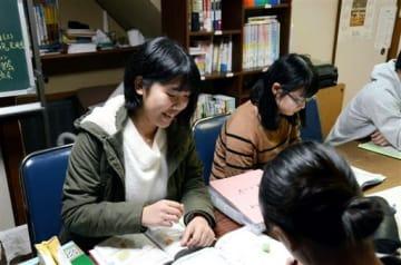 県立大への進学が決まり、支えてもらった無料学習塾で「今度は支える側に回りたい」と意欲を見せる今本紗那さん(左)=熊本市中央区