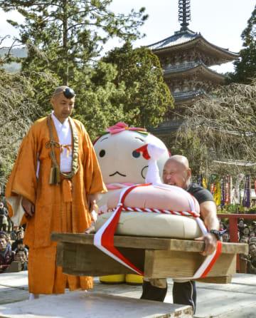 京都・醍醐寺の「餅上げ力奉納」で、特大の鏡餅を持ち上げる男性参加者=23日午後