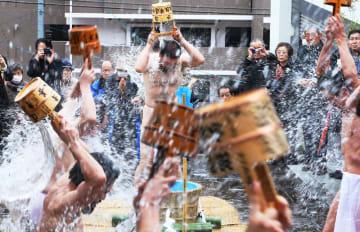 檀信徒が見守る中、水行を披露する山田副住職(中央)=長崎市、本蓮寺