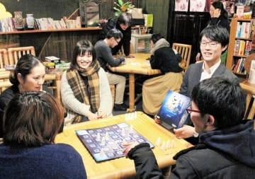 ボードゲームを楽しむ参加者。右は呼び掛け人の本多啓介さん=2月8日夜、福井県勝山市旭町2丁目の楽空茶