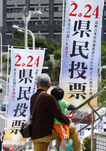 米軍普天間飛行場の沖縄県名護市辺野古への移設の賛否を問う、県民投票実施を伝えるのぼり旗=23日午後、那覇市