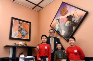 街角美術館がグランドオープンし、作品の前で笑顔を見せる葛迫幸平さん(左から2人目)と柊原小学校の児童=垂水市浜平の喫茶40