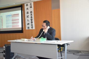 外国人からの110番通報を想定した訓練でタガログ語を通訳する参加者=県警本部