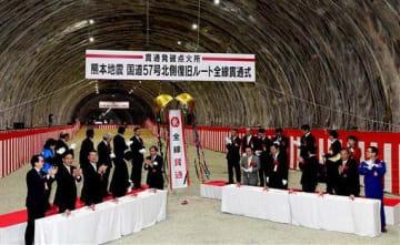 国道57号北側復旧ルートの二重峠トンネルが貫通し、拍手する蒲島郁夫知事(左側テーブルの前列右)や国会議員、関係自治体の首長ら=23日午前、大津町(小野宏明)