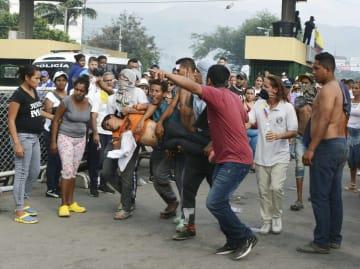23日、コロンビア北部ククタ近郊の国境にあるシモン・ボリバル橋で、負傷者を運ぶベネズエラの野党連合支持者ら(共同)