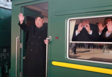 平壌駅で見送りに手を振る北朝鮮の金正恩朝鮮労働党委員長=23日(朝鮮中央通信=共同)