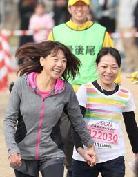 最後の走者と手をつないで走る高橋尚子さん(左)=姫路市本町、姫路城三の丸広場(撮影・吉田敦史)