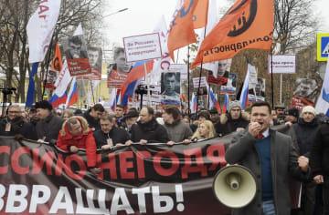 24日、モスクワで「プーチンのいないロシアを」などと叫びながら行進する参加者ら(共同)