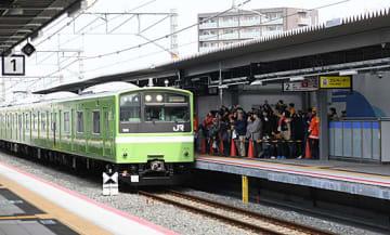 城北公園通駅のホームに到着した車両を撮影する参加者=24日、大阪市旭区