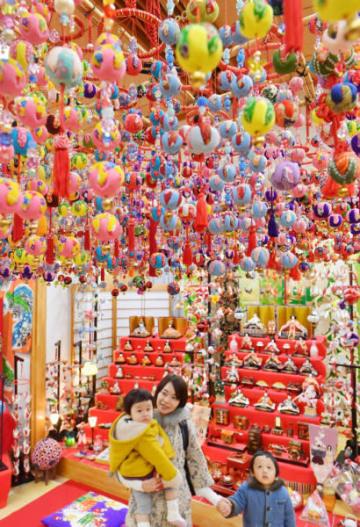 地元の女性たちが作った色鮮やかなつるし雛の展示に見入る親子=15日、花巻市石鳥谷町