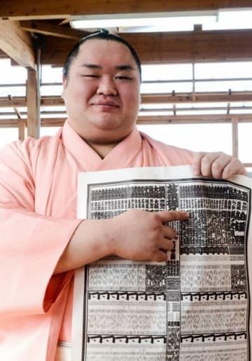 堺市の宿舎で新番付の名前を笑顔で指さす友風(24)=大阪府堺市