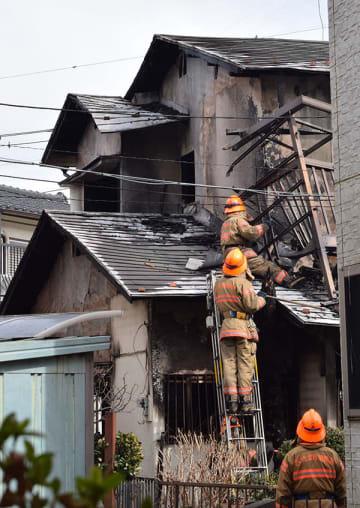 火災のあった住宅を調べる消防隊員=25日午後0時45分ごろ、さいたま市岩槻区宮町2丁目