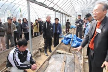吉田理事長(右)から生ごみなどを混ぜた土の作り方を学ぶ参加者=西海市大島町