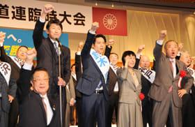 吉川自民党道連会長(前列)らとともに拳を突き上げる鈴木氏(右から3人目)