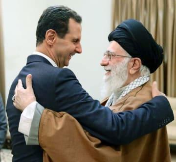 イラン・テヘランでの会談で、抱き合うハメネイ師(右)とシリアのアサド大統領=25日(ハメネイ師事務所提供・共同)