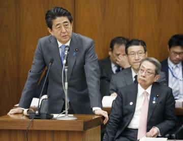 衆院総務委で答弁する安倍首相。右は石田総務相=26日午前