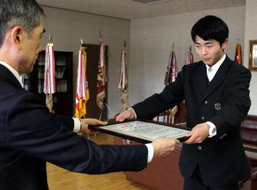 松浦鉄道の今里社長(左)から感謝状を受け取る平田さん=佐世保市、佐世保西高