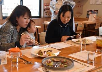 地元の食材を使った一流シェフの料理を楽しむ参加者
