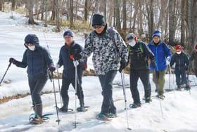 かんじきを履いて雪上を進む参加者たち