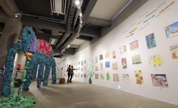 自由な発想で描かれた絵画と巨大な新聞紙製オブジェが「子どもから見える世界」にいざなう=市原市