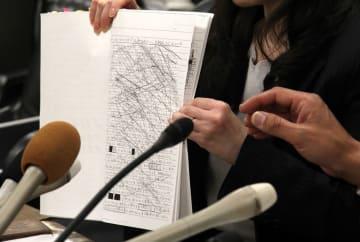 生徒が亡くなる前にいじめなどについて書き残したノートのコピーを手に説明する遺族=長崎県庁