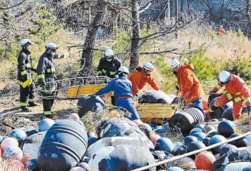 土砂に見立てて積んだ漁具や枯れ木の中から要救助者を探し出す参加者