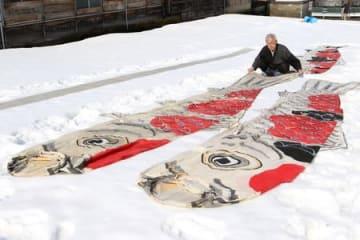 錦鯉のこいのぼりの雪さらしを行う樋口隆司さん=小千谷市本町2