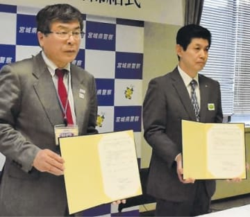 覚書を手にする紺野専務理事(左)と小野寺局長
