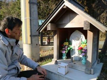 堤防から撤去した地蔵像を見つめる高橋さん(福知山市正明寺)