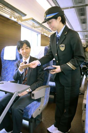 新快速の有料座席「Aシート」に着席後、乗客が乗務員に料金を支払うデモンストレーション=27日午後、兵庫県太子町