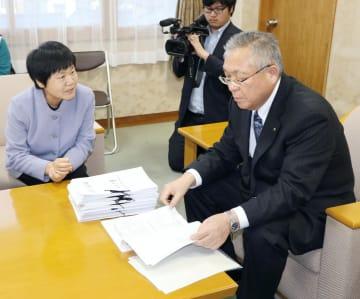 福島県南相馬市の門馬和夫市長(右)に署名を提出した地元住民=27日午後、南相馬市