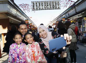 昨年12月、東京・浅草で記念撮影するシンガポールから訪れた家族