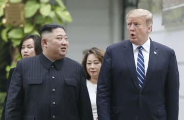 会談場のホテルの庭園で、並んで歩きながら会話するトランプ米大統領(右)と北朝鮮の金正恩朝鮮労働党委員長=28日、ハノイ(ロイター=共同)