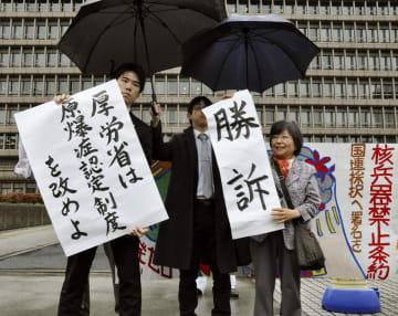 原爆症認定を巡る訴訟の判決を受け、「勝訴」と書かれた紙などを掲げる弁護士ら=28日午後、大阪地裁前
