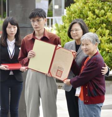 台北市で開かれた「2.28事件」の追悼式典で、蔡英文総統(右から2人目)から名誉回復の証書を受け取る事件犠牲者の遺族=28日(共同)