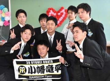 卒業式を終え、同級生と記念撮影する小幡(中央)