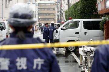 高齢女性が手足を縛られ死亡しているのが見つかった現場のマンション前で警戒にあたる警察官=28日午後、東京都江東区