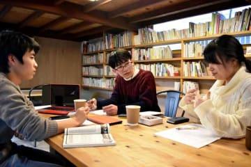 決勝を前に歌を持ち寄り、話し合う宮崎大短歌会チーム=2月、宮崎市内の飲食店