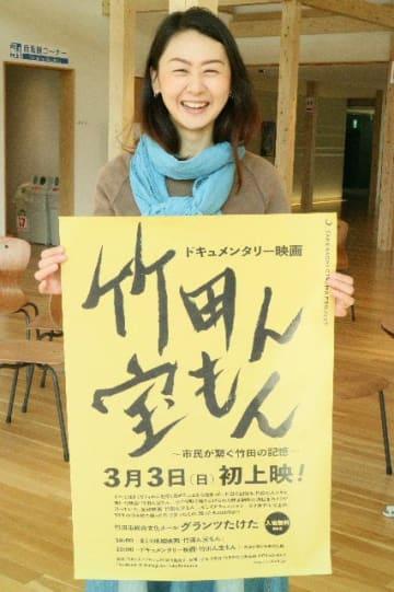 ポスターを手に上映を呼び掛けるプロジェクトリーダーの小笠原順子さん=26日、竹田市総合文化ホール