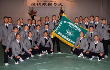 【選抜旗を中心に記念撮影する津田学園の選手ら=桑名市野田5丁目の同校で】