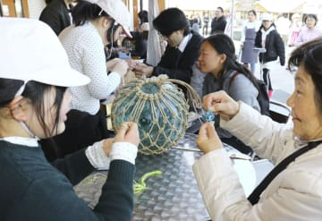 勝浦漁港で開かれたガラス製の漁具「ビン玉」を保護する縄を編む体験イベント=1日午後、和歌山県那智勝浦町