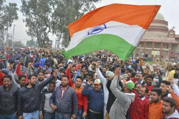 パキスタンとの国境地帯で、国旗を振ってインド空軍機操縦士の解放を待つインドの人たち=1日(AP=共同)