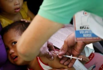 フィリピンのマニラで、子どもにはしかの予防接種をするボランティア=2月16日(AP=共同)
