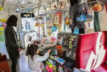 紀州鉄道のイベント列車で駄菓子を選ぶ子ども=2日午前、和歌山県御坊市