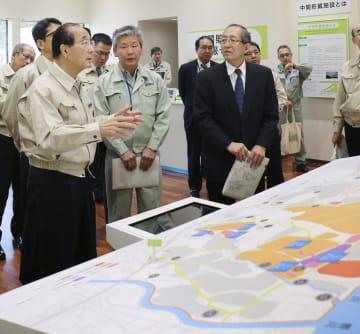中間貯蔵施設の事業に関する説明を受ける原田環境相(手前左)=2日午後、福島県大熊町