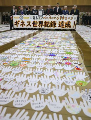 ギネス世界記録に認定された「最も長いペーパーハンドチェーン」。手の形に切り取った紙を1本のひもでつなげた=2日、大阪市