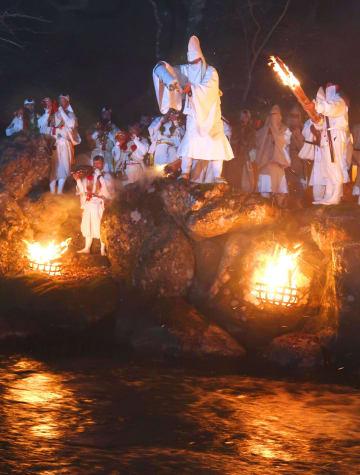 伝統行事「お水送り」で、遠敷川に「お香水」を注ぐ住職ら=2日夜、福井県小浜市